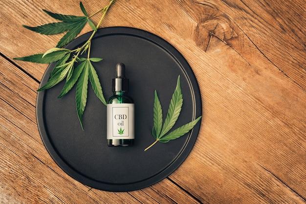 Prodotto medico di cannab, olio di cbd, con foglie di canapa su un piatto nero su un tavolo di legno. lay piatto. mockup copia spase