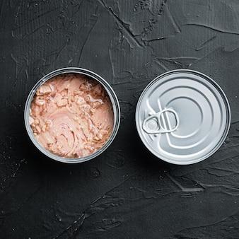 Servizio di tonno selvatico in scatola, in barattolo di latta, su fondo nero, formato quadrato
