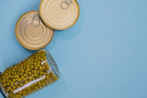 Cibo in scatola e piselli verdi su sfondo blu cibo per donazioni aiuto alimentare.