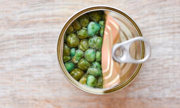 Conserve alimentari in metallo possono sul tavolo di legno, vista dall'alto - conserve di alimenti non deperibili per la conservazione degli alimenti in cucina, piselli in scatola