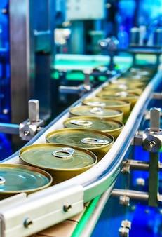 Conserve di prodotti alimentari sul nastro trasportatore nel magazzino di distribuzione.