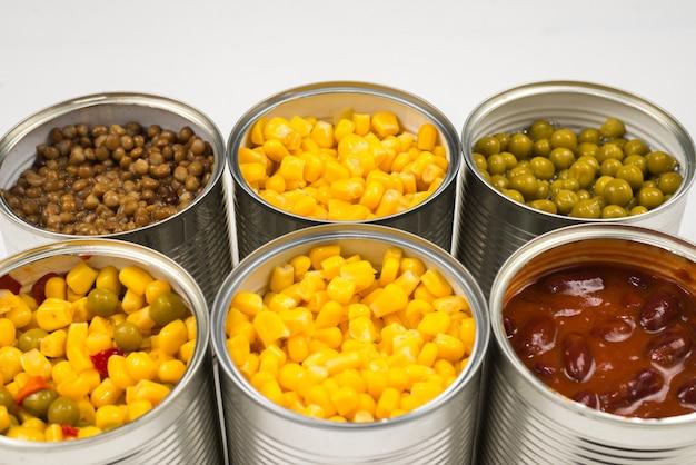Cibo in scatola su sfondo bianco. pisello, fagioli, mais, lenticchie.