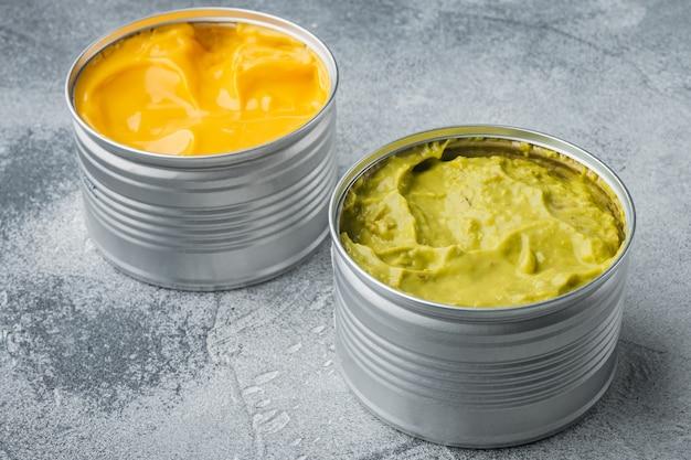 Guacamole in scatola e salsa di formaggio in lattina, su sfondo grigio