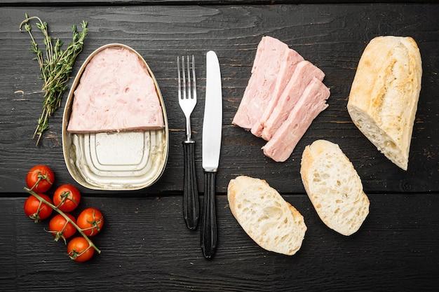 Set di panini al prosciutto in scatola, su sfondo di tavolo in legno nero, vista dall'alto piatta