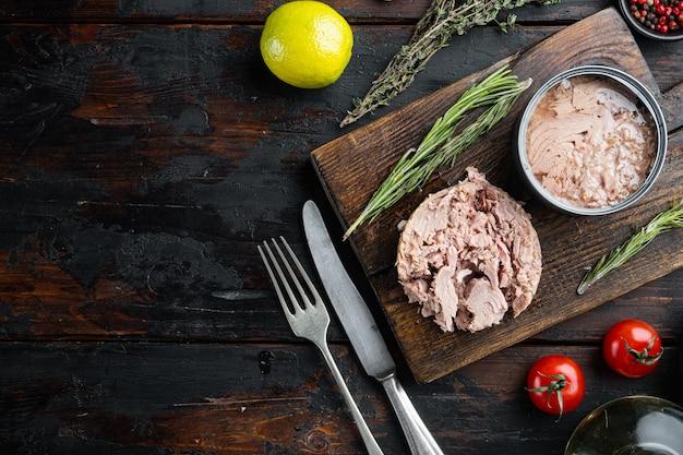Conserve di tonno italiano, sul tagliere di legno, sul vecchio tavolo di legno scuro