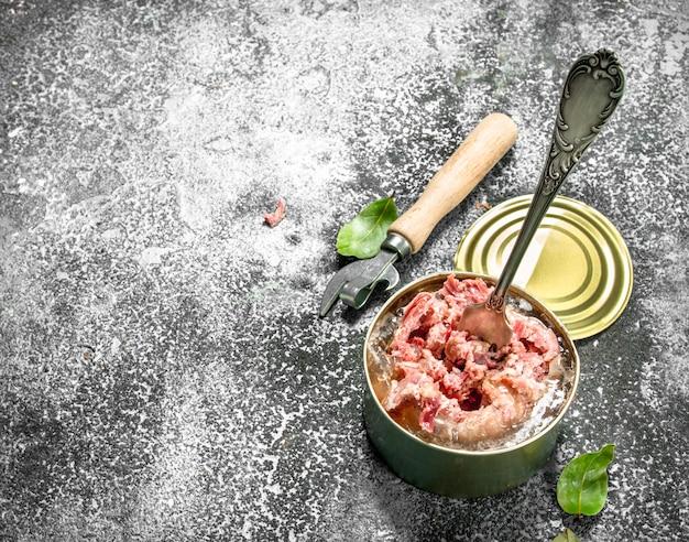 Conserve di carne in un barattolo di latta sul tavolo rustico.