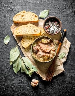 Conserve di carne in una teglia su carta con fette di pane. sul nero rustico