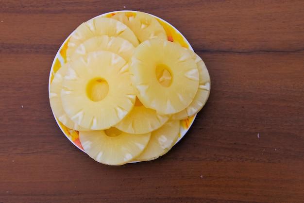 Ananas in scatola su un piatto sul tavolo di legno