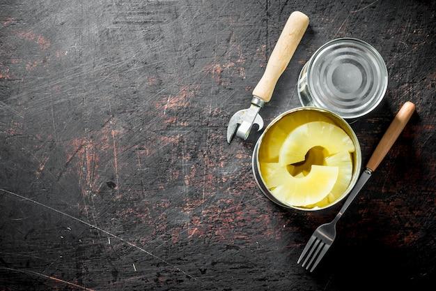 Ananas in scatola in un barattolo di latta sul tavolo rustico scuro.