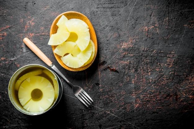 Ananas in scatola in un barattolo di latta e su un piatto. su fondo rustico scuro