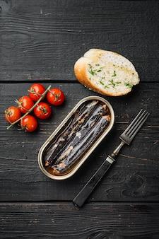 Frutti di mare in scatola conservati in olio, su sfondo di tavolo in legno nero, vista dall'alto piatta, con spazio di copia per il testo