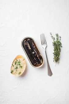 Frutti di mare in scatola conservati in olio, su sfondo di tavolo in pietra bianca, vista dall'alto piatta, con spazio di copia per il testo