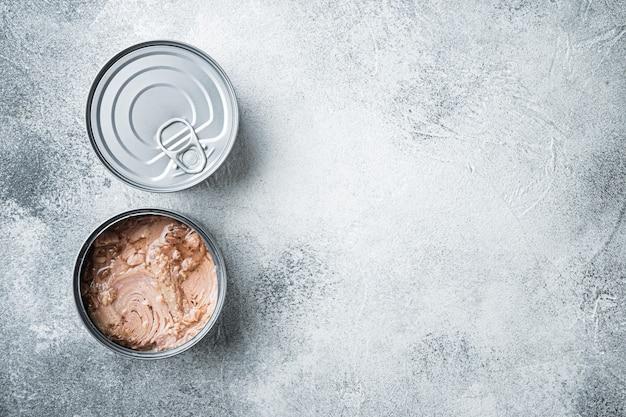 Set di tonno bianco senza soia in scatola, in barattolo di latta, sul tavolo grigio, vista dall'alto laici piatta