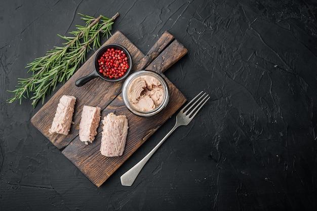 Filetto di tonno in scatola in olio d'oliva su fondo nero, piatto
