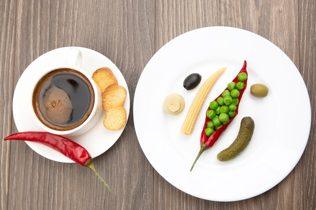 Insalata di verdure in scatola e una tazza di caffè nero con pepe rosso e cracker sui piatti