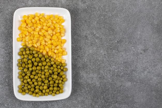 Piatto bianco di verdure in scatola pieno di piselli e semi di mais dolce