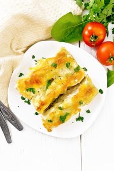 Cannelloni ripieni di ricotta e spinaci con salsa besciamella in un piatto, tovagliolo, pomodori e prezzemolo su sfondo di tavola di legno dall'alto