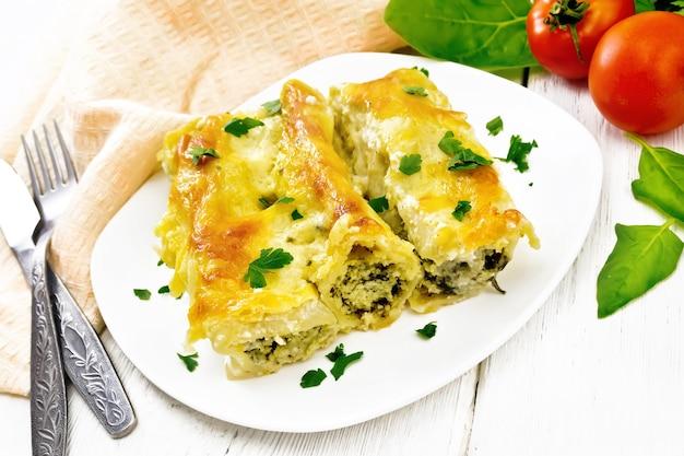 Cannelloni ripieni di ricotta e spinaci con salsa besciamella in un piatto, asciugamano, pomodori e prezzemolo su uno sfondo di tavola di legno bianco