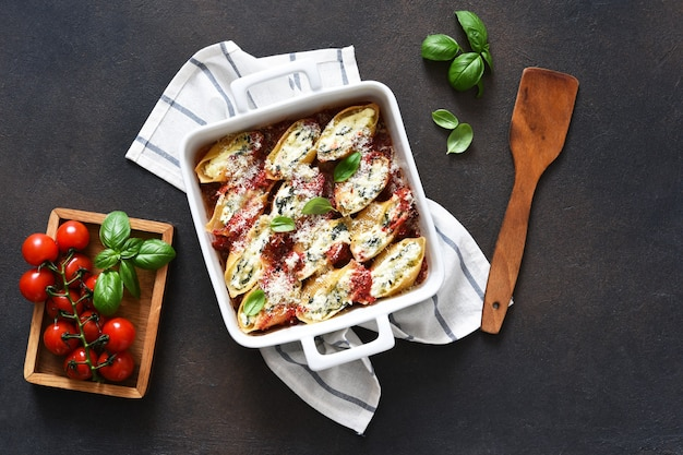 Cannelloni con ricotta e spinaci al forno in salsa di pomodoro con parmigiano.pasta al forno con ricotta.