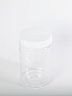 Lattine per la conservazione di prodotti sfusi con coperchi bianchi su sfondo chiaro e isolato. contenitore in plastica trasparente con coperchio per conservare alimenti e prodotti sfusi. un barattolo vuoto per il cibo. copia spazio