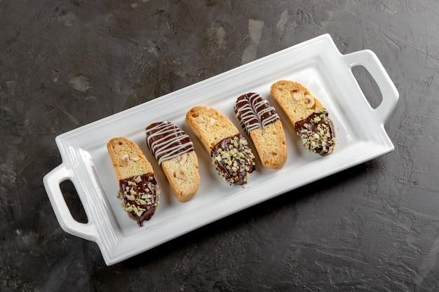 Biscotti di cantuccini con cioccolato e pistacchi sul piatto bianco, su fondo di pietra.