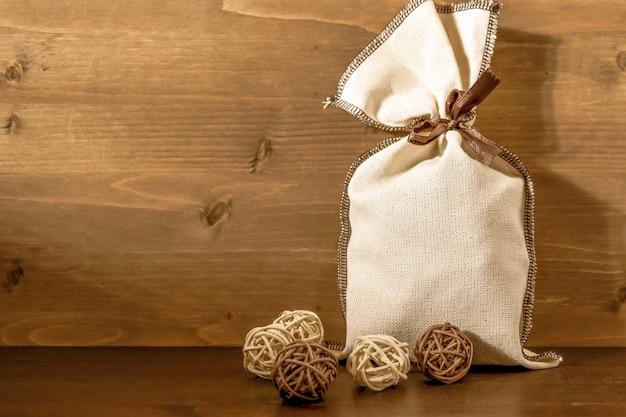 Borsa di tela con regali accanto a piccole palline decorative in vimini, su fondo di legno marrone. concetto: regalo per il nuovo anno, natale, cartolina. copia spazio.
