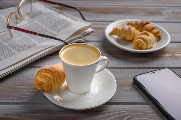 Tappo di caffè e biscotti fatti in casa bagel su una superficie di legno vicino a smartphone giornale e bicchieri