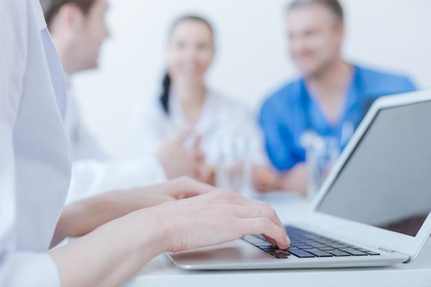 Abile giovane medico professionista utilizzando il computer portatile presso la clinica e digitando mentre i suoi colleghi discutono dietro
