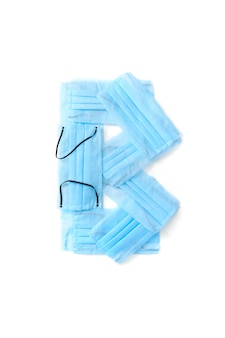 Lettera maiuscola b fatta a mano da maschere per il viso blu protettive antibatteriche mediche su un muro bianco, copia dello spazio. alfabeto creativo per inventare nuove parole.
