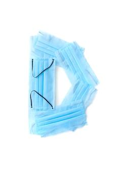 Lettera maiuscola d fatta a mano da maschere per il viso blu protettive antibatteriche mediche su un muro bianco, copia dello spazio. alfabeto creativo per inventare nuove parole.