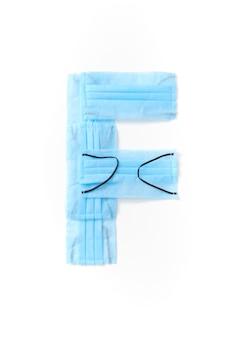 Lettera maiuscola f fatta a mano da maschere protettive blu mediche antibatteriche su un muro bianco, copia dello spazio. alfabeto creativo per inventare nuove parole.