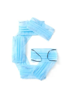 Lettera maiuscola g fatta a mano da maschere per il viso blu protettive antibatteriche mediche su un muro bianco, copia dello spazio. alfabeto creativo per inventare nuove parole.