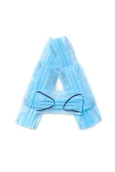 Lettera maiuscola a fatto a mano da maschere protettive blu mediche antibatteriche su un muro bianco, copia spazio. alfabeto creativo per inventare nuove parole.