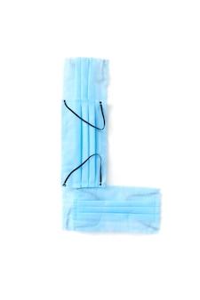 Lettera maiuscola l fatta a mano da maschere protettive blu mediche antibatteriche su un muro bianco, copia dello spazio. alfabeto creativo per inventare nuove parole.
