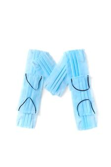 Lettera maiuscola m fatto a mano da maschere protettive blu mediche antibatteriche su un muro bianco, copia dello spazio. alfabeto creativo per inventare nuove parole.