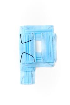 Lettera maiuscola p fatta a mano da maschere per il viso blu protettive antibatteriche mediche su un muro bianco, copia dello spazio. alfabeto creativo per inventare nuove parole.