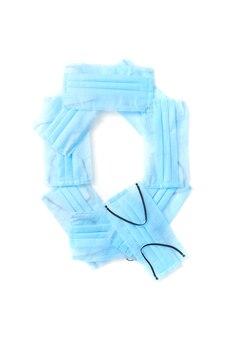 Lettera maiuscola q fatta a mano da maschere protettive blu mediche antibatteriche su un muro bianco, copia dello spazio. alfabeto creativo per inventare nuove parole.
