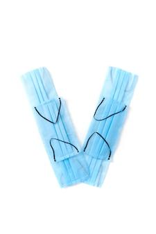 Lettera maiuscola v fatta a mano da maschere protettive blu mediche antibatteriche su un muro bianco, copia dello spazio. alfabeto creativo per inventare nuove parole.