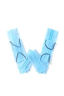 Lettera maiuscola w fatta a mano da maschere protettive blu mediche antibatteriche su un muro bianco, copia dello spazio. alfabeto creativo per inventare nuove parole.