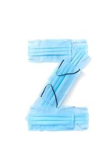 Lettera maiuscola z fatta a mano da maschere per il viso blu protettive antibatteriche mediche su un muro bianco, copia dello spazio. alfabeto creativo per inventare nuove parole.