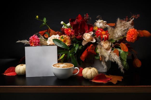 Cappuccino e bellissimi fiori ancora in vita. composizione negozio di fiori. tazza di caffè, mela, fresca e bouquet sulla tavola di legno nera. arte fiorista e concetto di design floreale