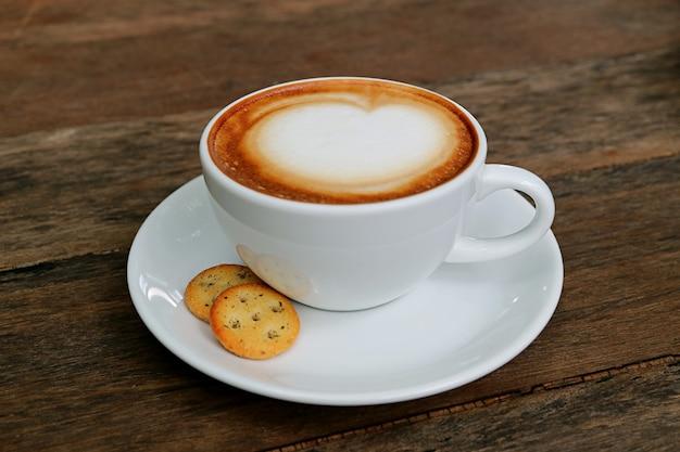 Caffè cappuccino con un paio di cracker isolati su un tavolo di legno