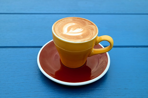 Caffè cappuccino in tazza marrone giallo isolato sulla tavola di legno blu