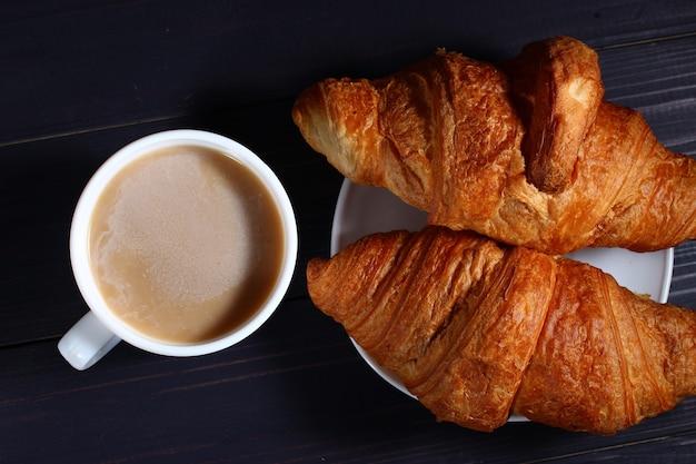Cappuccino e croissant su un buio