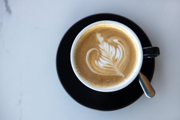 Tazza del cappuccino sul piattino nero sul fondo di marmo bianco della tavola. latte design. copia spazio. vista dall'alto, piatto. orizzontale. per i social media, blog di cucina. concept bevande senza lattosio, caffè decaffeinato.