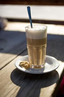 Di cappuccino in vetro sulla tavola di legno al giorno soleggiato