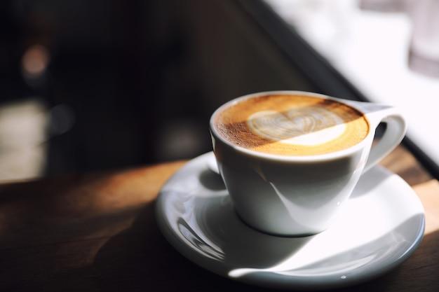 Cappuccino o latte art caffè a base di latte sul tavolo di legno nella caffetteria