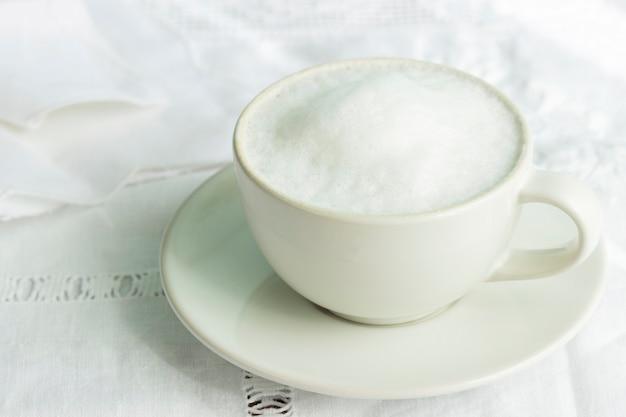 Cappuccino in una tazza leggera su una tovaglia vintage. messa a fuoco selettiva.