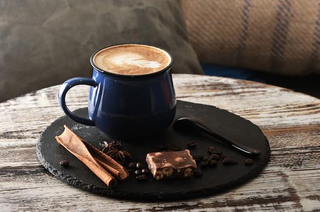 Cappuccino in una tazza con schiuma di latte e cannella e cioccolato