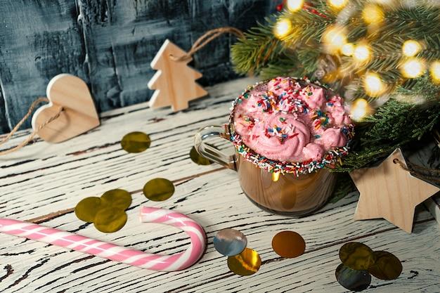 Cappuccino, marshmallow rosa, ramo di abete, bastoncino di zucchero su fondo rustico per natale
